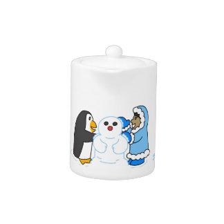 Pingüino y chica que hacen un muñeco de nieve