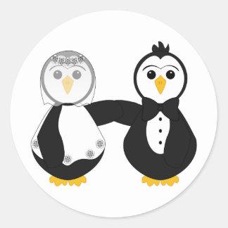 Pingüinos casados que llevan a cabo las manos etiqueta redonda