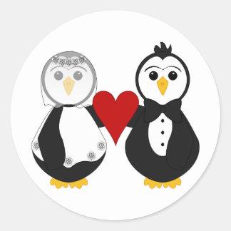 Pingüinos casados que llevan a cabo un corazón pegatina redonda
