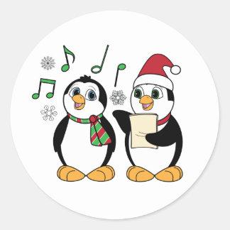 Pingüinos de Caroling en el pegatina de la nieve
