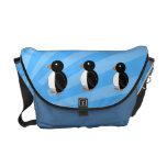 Pingüinos en la bolsa de mensajero azul del respla bolsas de mensajeria