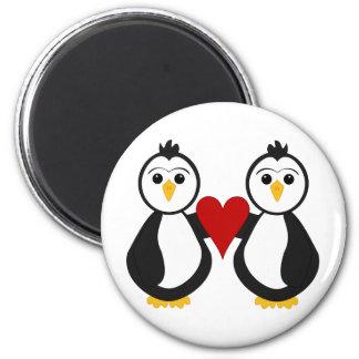 Pingüinos lindos que llevan a cabo un corazón imán redondo 5 cm