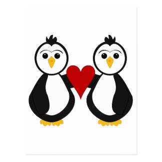 Pingüinos lindos que llevan a cabo un corazón postal