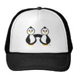 Pingüinos que llevan a cabo las manos gorras de camionero