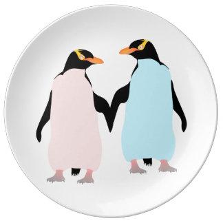 Pingüinos rosados y azules que llevan a cabo las platos de cerámica
