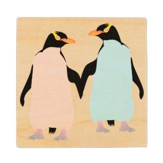 Pingüinos rosados y azules que llevan a cabo las posavasos de arce