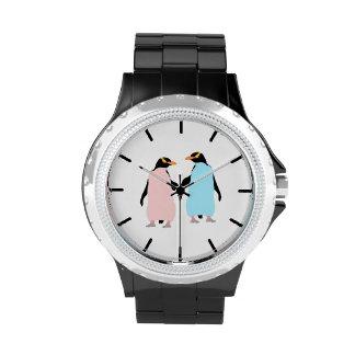 Pingüinos rosados y azules que llevan a cabo las relojes de mano
