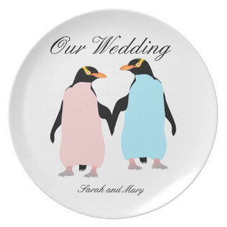 Pink and blue Penguins holding hands. Plate
