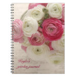 pink and white ranunculus on script notebook