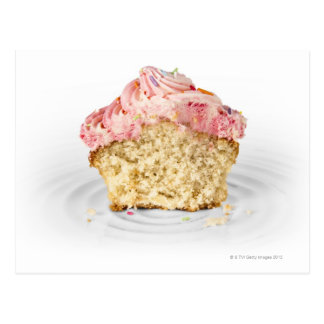 Pink cup cake sat on a porcelain cake stand, on postcard