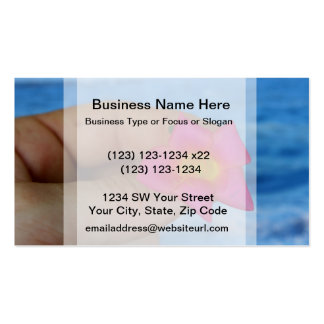 pink flower in fingers against blue business cards