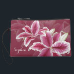 "Pink Lillies Suede Wristlet<br><div class=""desc"">A ruby background color with painted stargazer lillies in shades of pink,  red,  and white.  Add your name to the text field or clear it out if wish.  You can also click on &quot;Customize It!&quot; to adjust the font type,  size,  color,  placement,  etc.  Artwork and design by Karlajkitty.</div>"