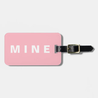 Pink luggage tag with 'Mine' written on it