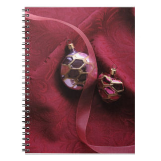 pink ornaments on red fabric notebook