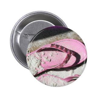Pink sandy flip flop sandals on Florida beach Button