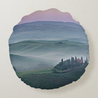 Pink sunrise over a Tuscany landscape round pillow