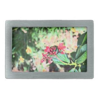 pink wax flower against green floral rectangular belt buckle