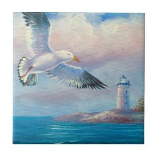 Pintura de una gaviota que vuela cerca de un faro azulejo
