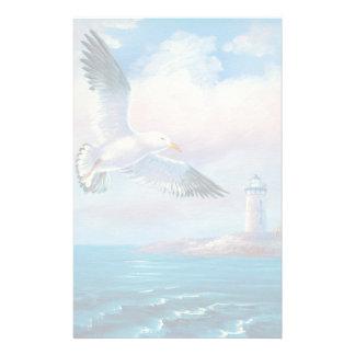 Pintura de una gaviota que vuela cerca de un faro papeleria personalizada