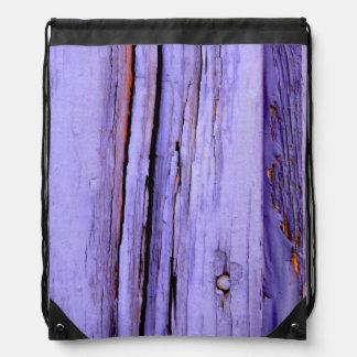 Pintura púrpura agrietada vieja en la madera mochila