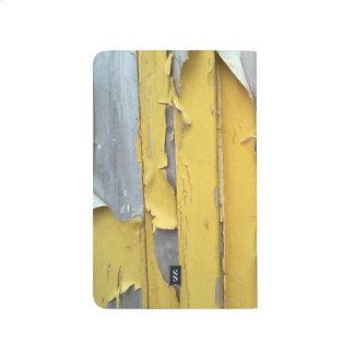 pintura que forma escamas amarilla de la pared cuaderno