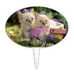 Pío juguetón de los gatitos fuera de una cesta de  decoraciones de tartas