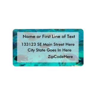 Piscina azul de los cichlids que nadan alrededor d etiquetas de dirección