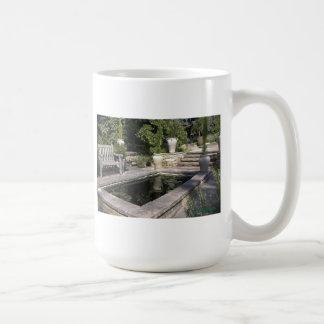 Piscina de reflejo en un jardín tazas de café