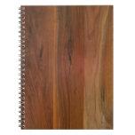 Piso de madera oscuro del grano libro de apuntes con espiral
