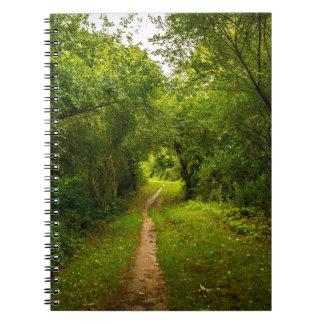 Pista de senderismo a través de las maderas libros de apuntes con espiral