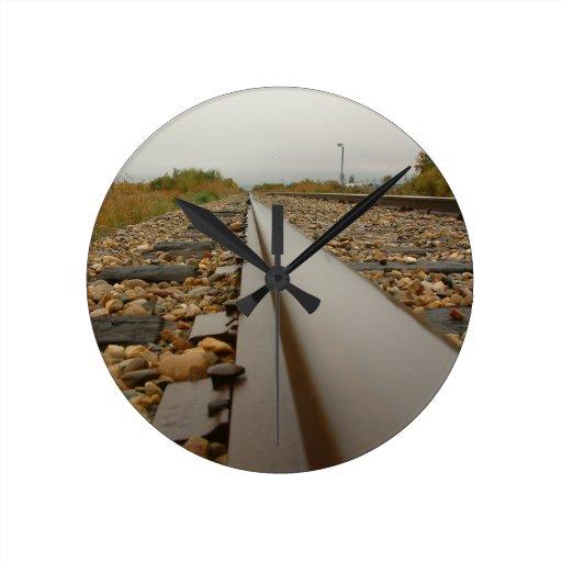 Pistas de ferrocarril en un día lluvioso reloj redondo mediano