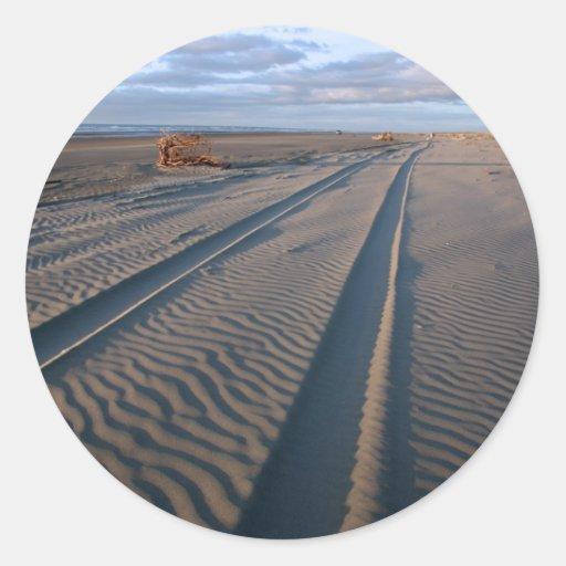 Pistas de vehículo en la playa arenosa Nueva Zelan Etiquetas