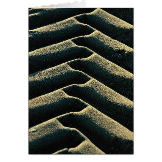 Pistas del neumático en la playa tarjeton