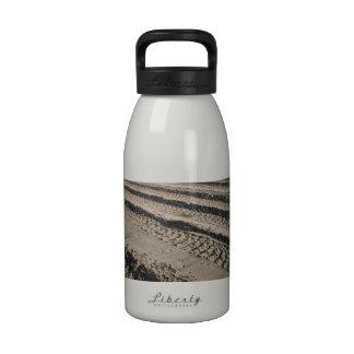 Pistas del neumático en suciedad botellas de agua reutilizables