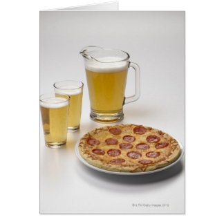 Pitcher and two pints of beer beside pepperoni greeting card