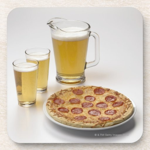 Pitcher and two pints of beer beside pepperoni drink coaster