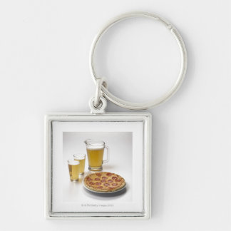 Pitcher and two pints of beer beside pepperoni keychain