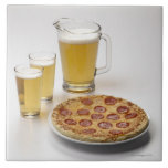 Pitcher and two pints of beer beside pepperoni large square tile