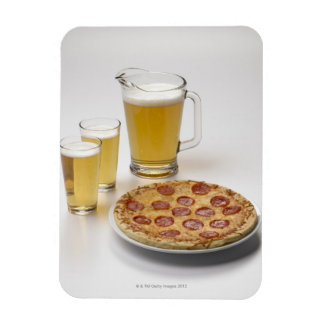 Pitcher and two pints of beer beside pepperoni magnet