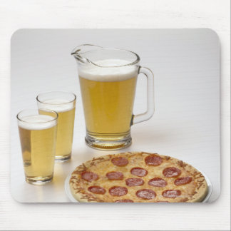 Pitcher and two pints of beer beside pepperoni mouse pad