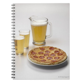 Pitcher and two pints of beer beside pepperoni note books