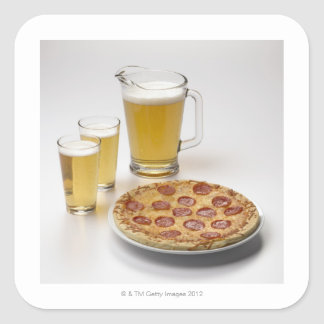 Pitcher and two pints of beer beside pepperoni square sticker