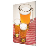 Pitcher of beer and two glasses filled with beer stretched canvas print