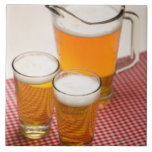 Pitcher of beer and two glasses filled with beer ceramic tiles