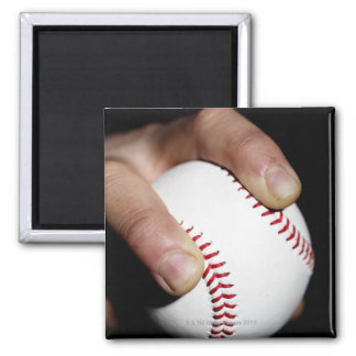 Pitchers hand gripping a baseball magnet