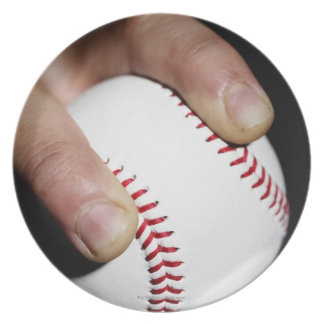 Pitchers hand gripping a baseball plate
