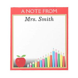 Pizarra y lápices coloreados una nota del profesor bloc de papel