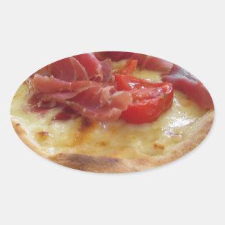 Pizza italiana original con el jamón, los tomates pegatina ovalada