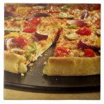 Pizza vegetal cortada en la cacerola negra en la azulejo cuadrado grande