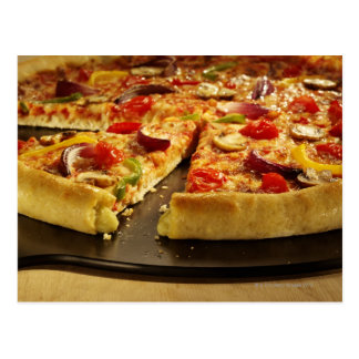 Pizza vegetal cortada en la cacerola negra en la m postales